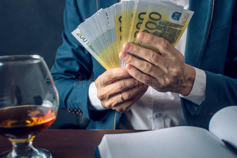 Manaffärsmannen i dräkt sätter pengar i hans fack En muta i form av euroräkningar Begrepp av korruption och bestickning arkivfoto