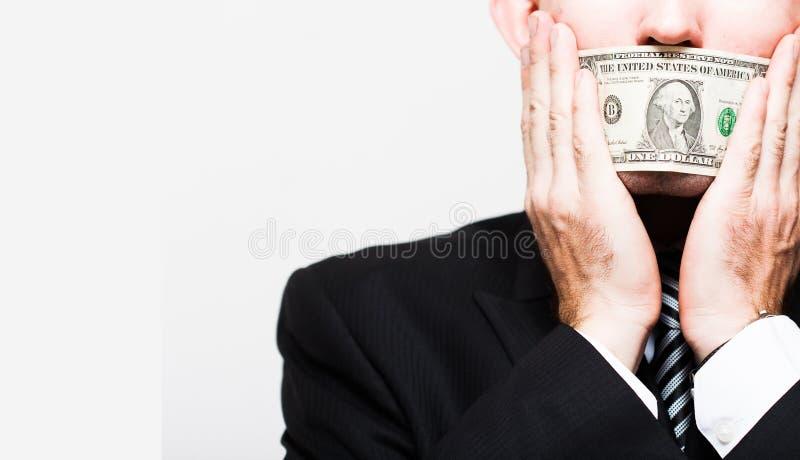Manaffärsmannen i en dräkt med stängda räkningar för en en dollar skvallrar, tyst för pengar begreppet av korruption och bestickn royaltyfria foton