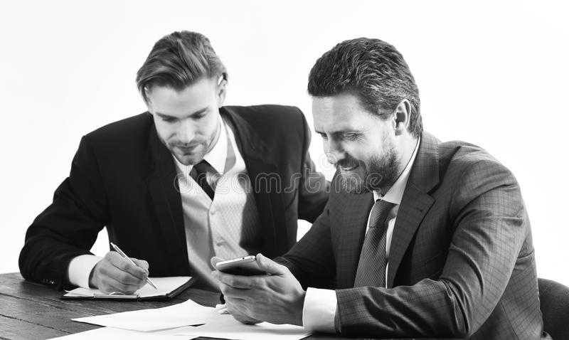 Management, leadership concept. CEO gives instructions to office worker. Business partners work with documents and smartphone. Busy people with smiling faces stock images