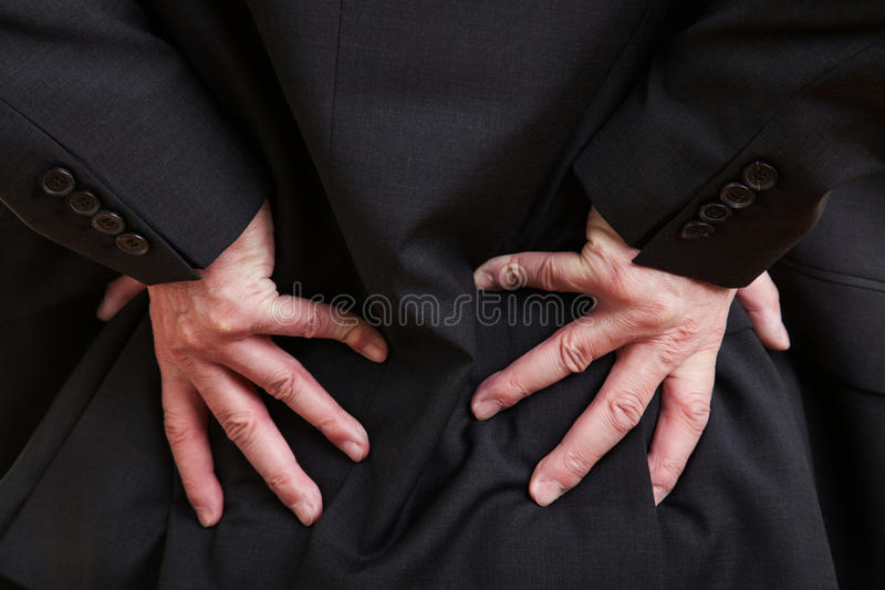 Manager with aching hip. Elderly businessman holding his hand to his aching back stock photography