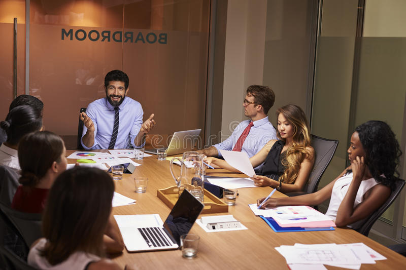 Manager addressing team at an evening business meeting royalty free stock photography