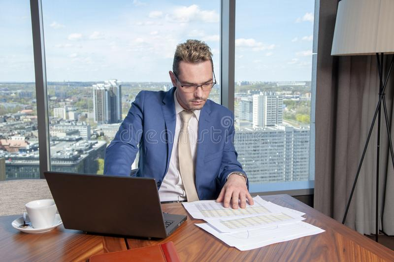 The manager behind the desk in the office hard work on the data. The manager behind the desk in the office hard work on the data stock images
