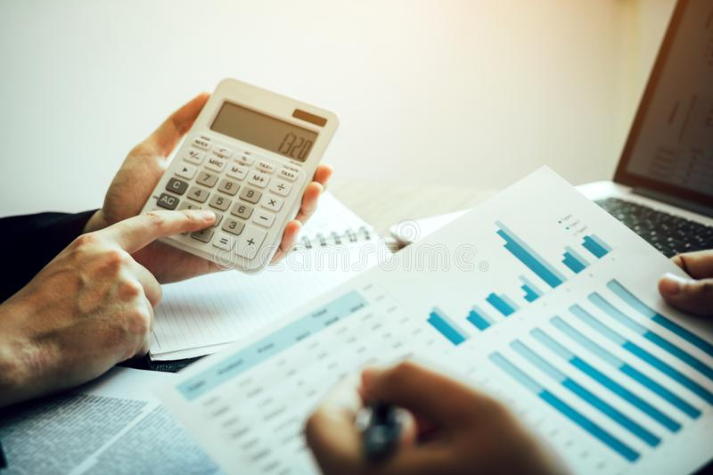 Manager calculates about the company finances by pressing on the calculator on the table with the employee explaining the summary. Report of the company cost at royalty free stock photo