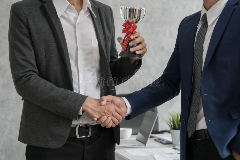Manager giving employee a trophy