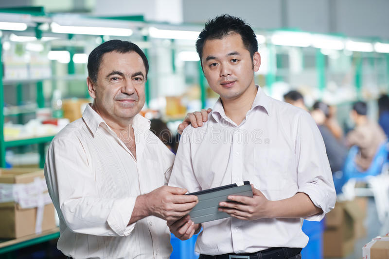 Manager and chinese worker in factory. Caucasian businessman manager and male chinese worker men in china factory manufacturing production royalty free stock photo