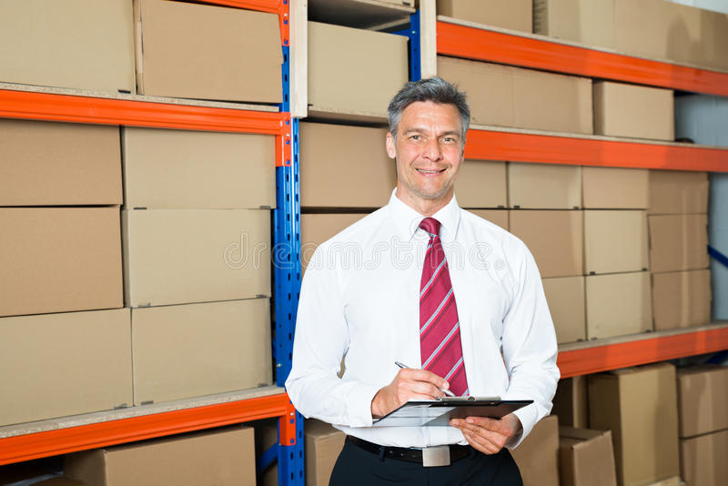 Manager With Clipboard In Distribution Warehouse royalty free stock images