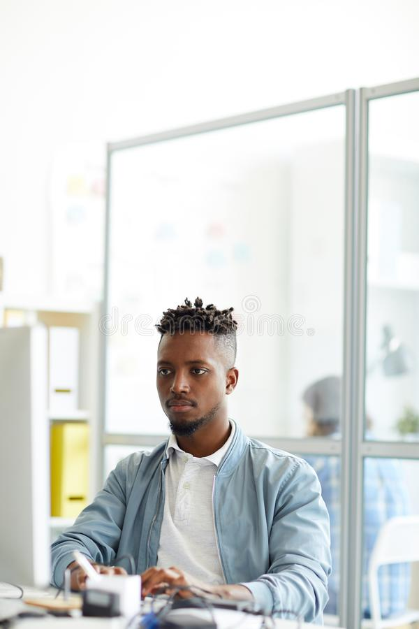 Manager by computer. Young African-american hipster sitting by workplace in front of computer monitor and learning new code language stock photo