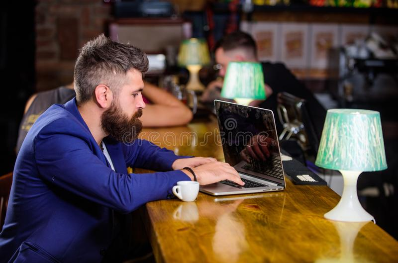 Manager create post enjoy coffee. Hipster freelancer work online drinking coffee. Coffee break concept. Man bearded stock photography