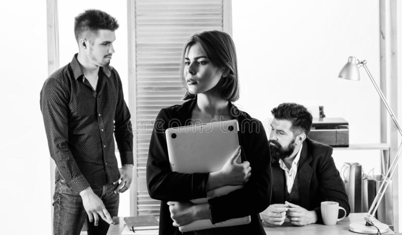 Manager creating a pleasant work environment. Sensual office manager with coworkers on background. Project manager with stock photos