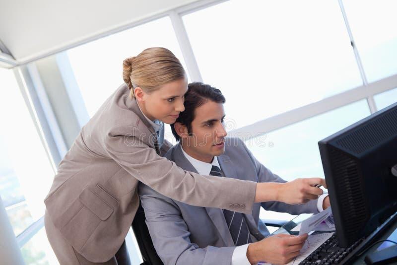 Manager, der auf etwas auf einem Computer zeigt lizenzfreie stockfotografie
