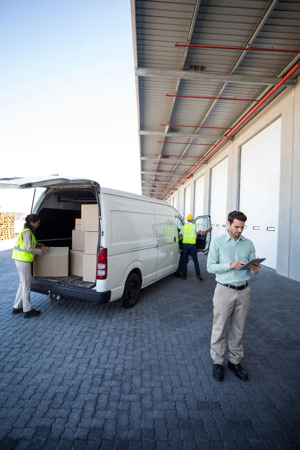 Manager, der an den Tabletten- und Lagerarbeitskräften laden die Pappschachteln arbeitet stockfoto
