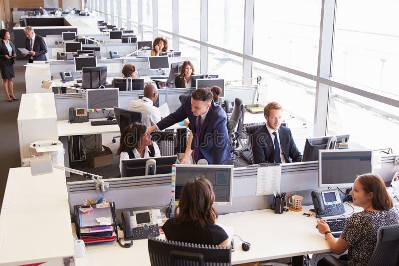 Manager in der Diskussion mit Mitarbeiter in einem Bürogroßraum stockfotografie
