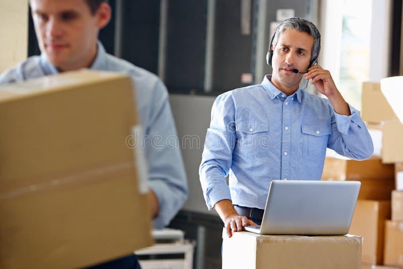 Manager, der Kopfhörer im Lagerhaus verwendet lizenzfreies stockbild