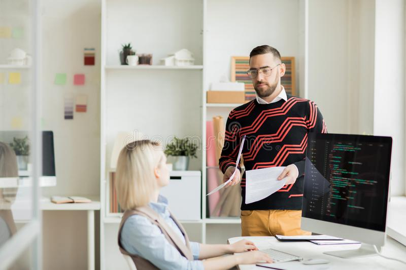 Manager, der Papier mit Aufgabe zur Kodierung des Spezialisten gibt stockbild