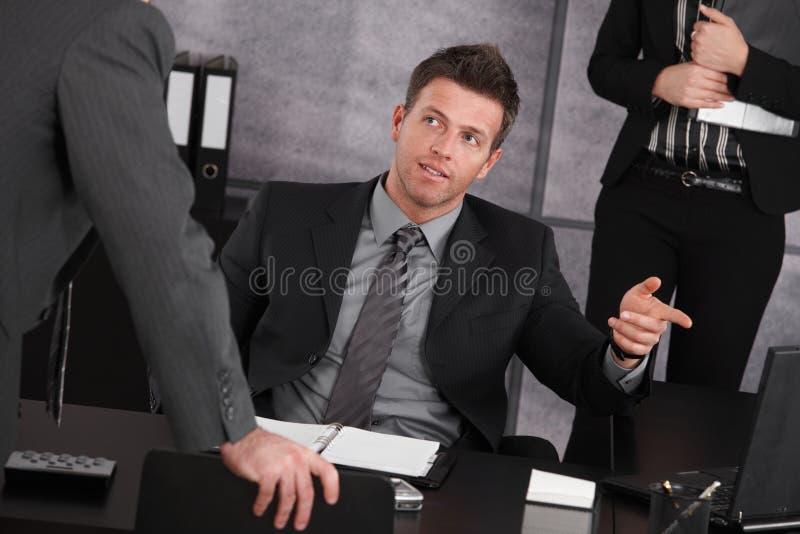Manager, der am Schreibtisch, unterrichtender Angestellter sitzt lizenzfreie stockfotos