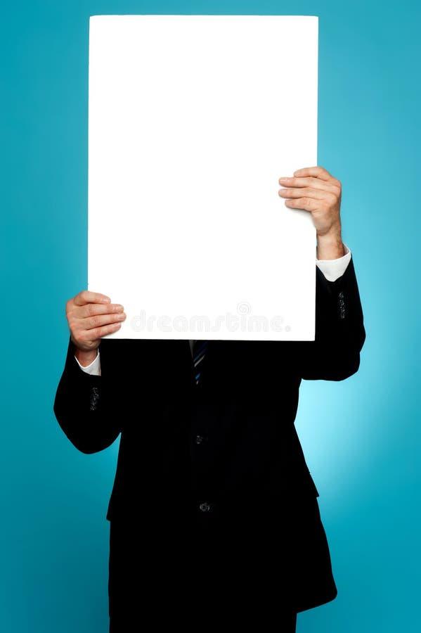 Manager, der sein Gesicht hinter weißer Fahnenanzeige versteckt lizenzfreie stockbilder