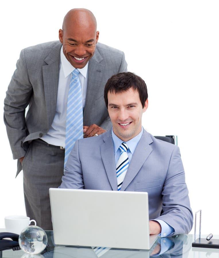 Manager, der seinen Kollegen an einem Computer unterstützt lizenzfreie stockbilder