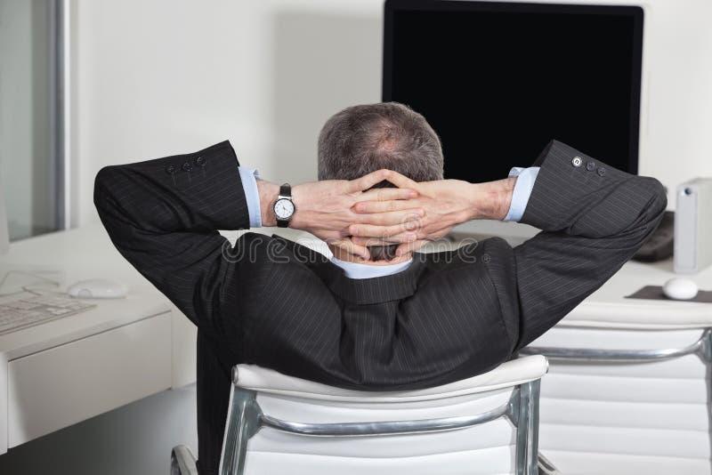 Manager, der sich zurück im Büro lehnt stockfotos