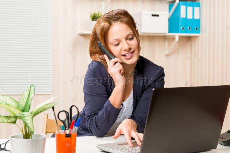 Manager, der am Telefon spricht und an dem Computer arbeitet stockbild