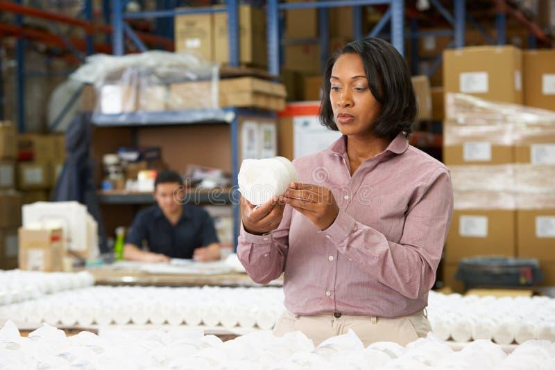 Manager, der Waren auf Fertigungsstraße überprüft lizenzfreies stockfoto