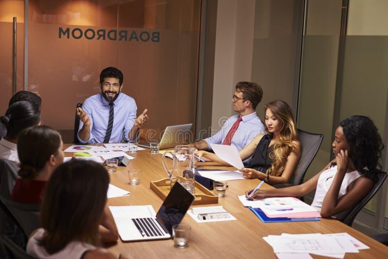 Manager, der zu Team bei einem AbendGeschäftstreffen spricht lizenzfreie stockfotografie
