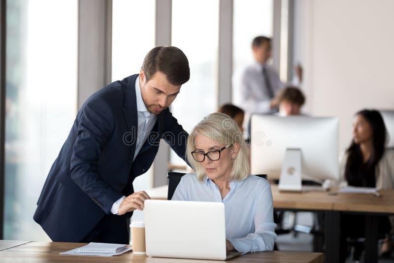 Manager des leitenden Angestellten, der den reifen Angestellten hilft mit Computer konsultiert lizenzfreie stockbilder