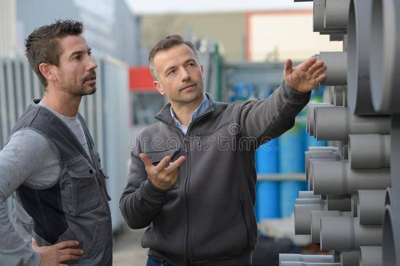 Manager dicussing aboout steel pipes circle pipe in factory. Pipes royalty free stock photos