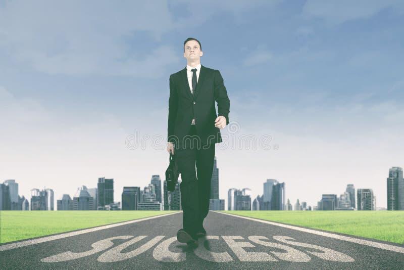 Manager die boven succeswoord lopen op de weg stock foto's