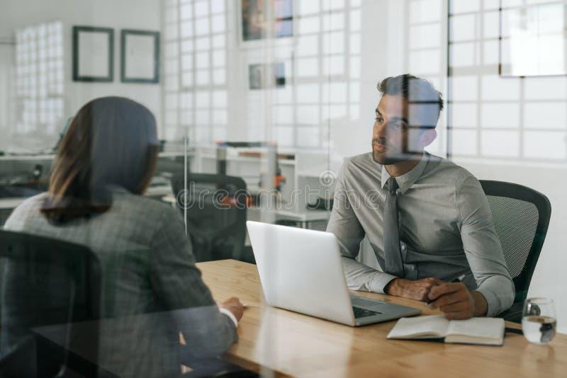 Manager die een baanaanvrager binnen van zijn bureau interviewen stock afbeeldingen