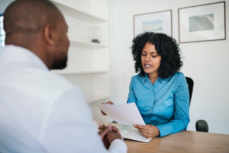 Manager die een samenvatting lezen tijdens een gesprek in haar bureau royalty-vrije stock afbeelding