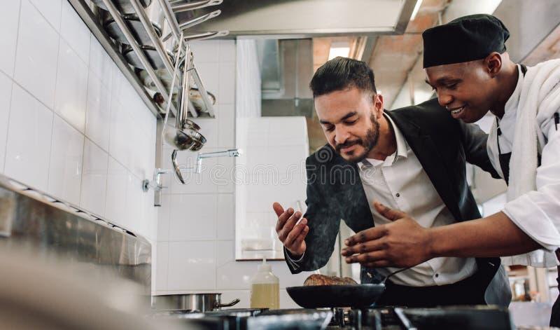 Manager die het aroma van voedsel met chef-kok ruiken royalty-vrije stock foto's