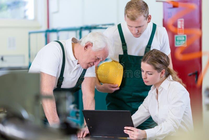 Manager die met installatiearbeiders spreken stock afbeeldingen