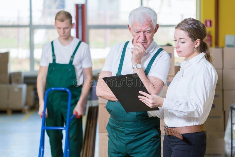 Manager die met pakhuisarbeider spreken stock afbeelding