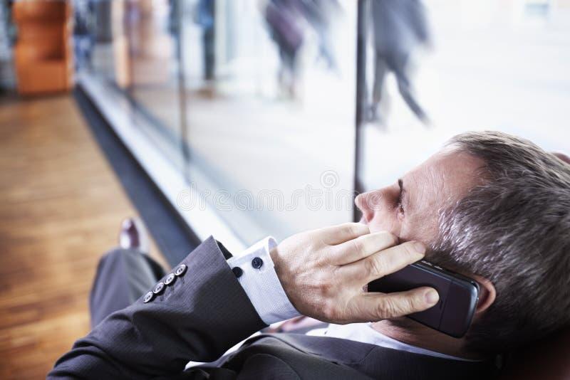 Manager die op telefoon, mensen op achtergrond spreekt. royalty-vrije stock foto