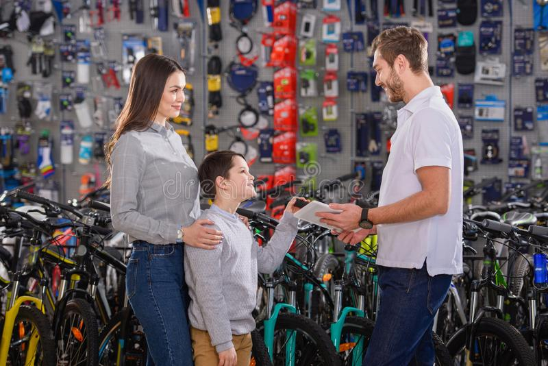 manager with digital tablet helping to choose bicycles to customers stock image