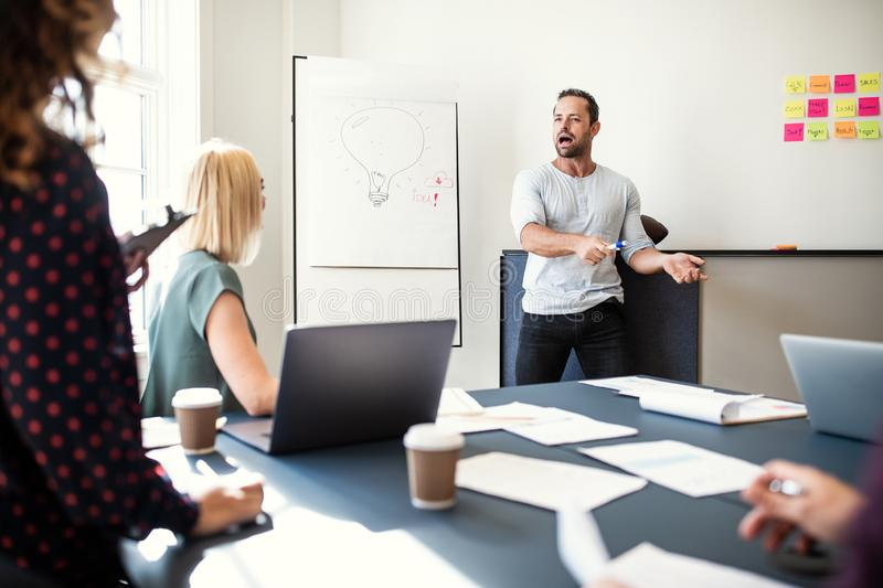 Manager doing a presentation to staff in an office stock image