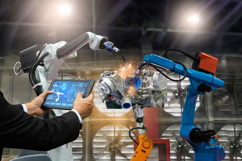 Manager engineer touch screen control automation robot arms the production of factory parts engine manufacturing industry robots a royalty free stock photography