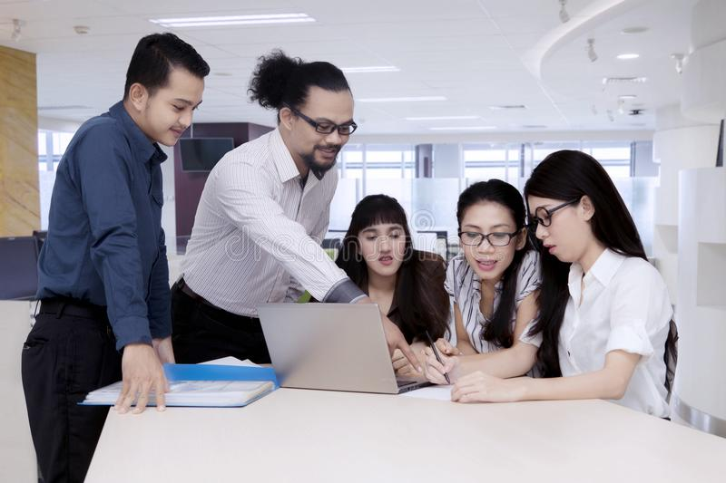 Manager explaining business goals from a laptop to employees.  royalty free stock image