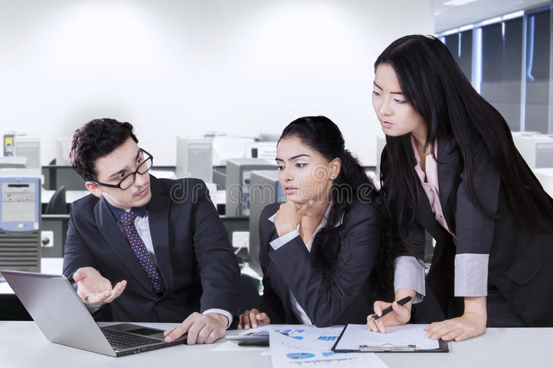 Manager explaining document at his team royalty free stock image