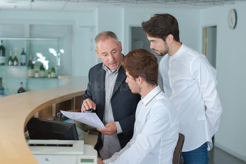 Manager explaining something to employee in reception stock image