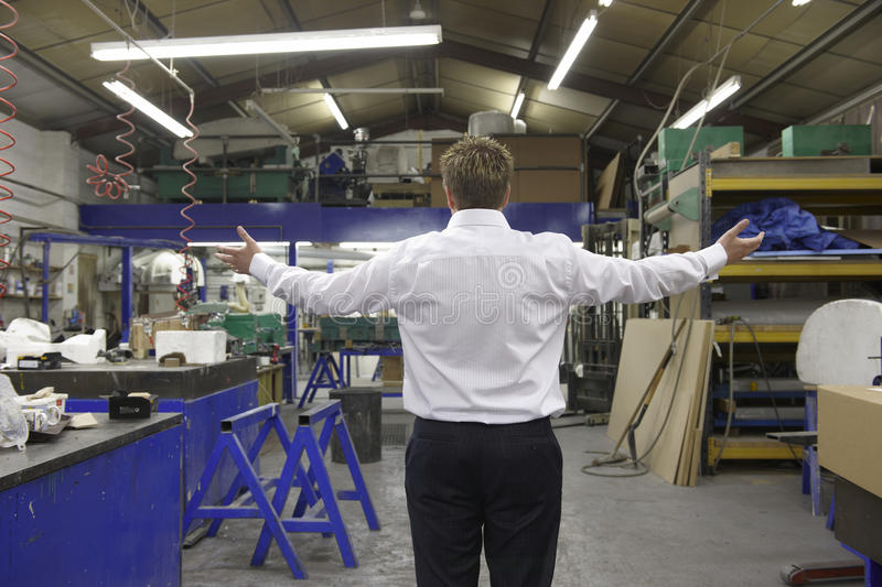 Manager on factory floor. Young manager looking at empty factory floor with arms outstretched royalty free stock image