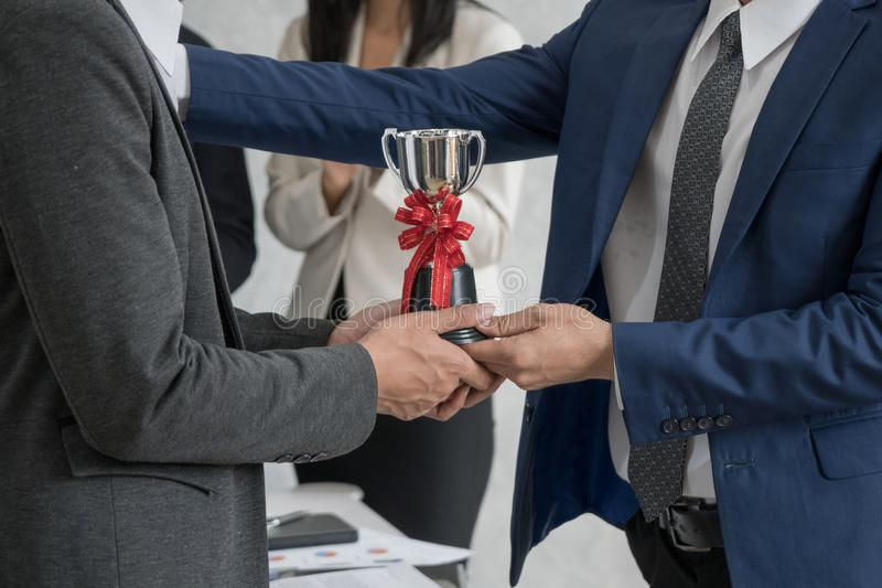 Manager giving employee the trophy award for success in business stock photography
