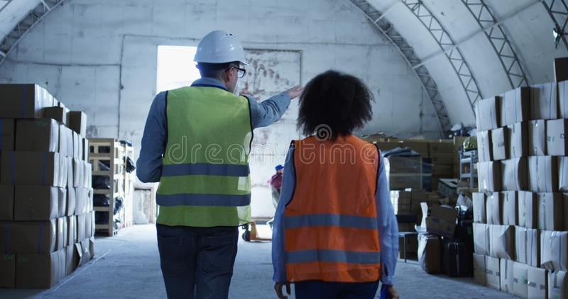 Manager giving out instruction in a warehouse. Medium long shot of manager giving out instruction in a warehouse royalty free stock photo