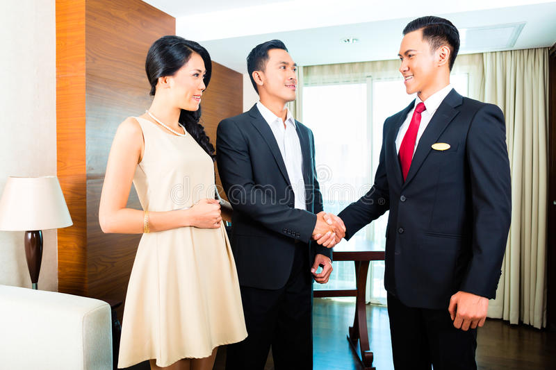 Manager greeting guests in Asian hotel royalty free stock photos