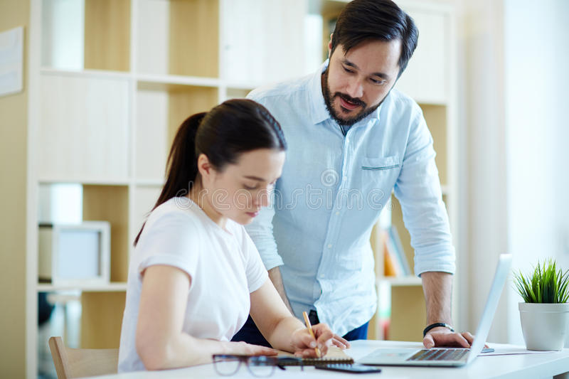 Manager Helping Trainee in office stock image