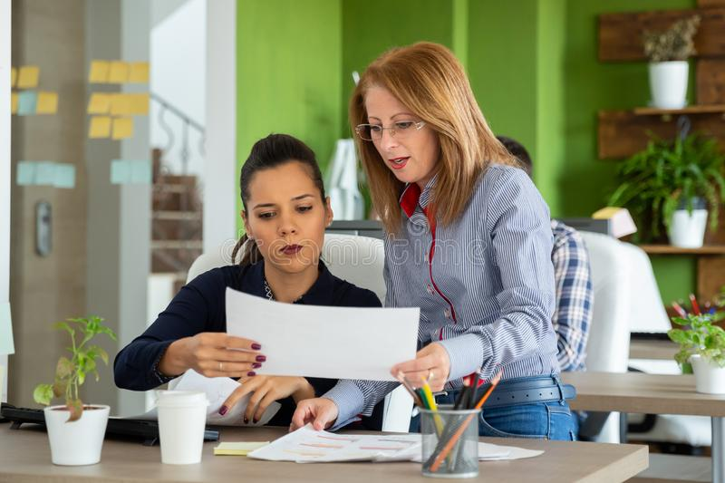 Manager in her 40s next to a young employee royalty free stock photo