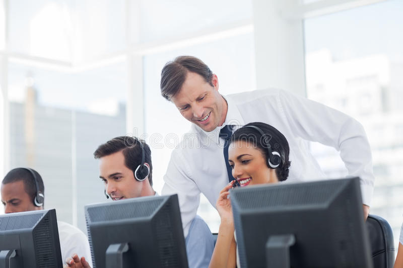 Manager listening to call centre employee. Working on computer stock photos