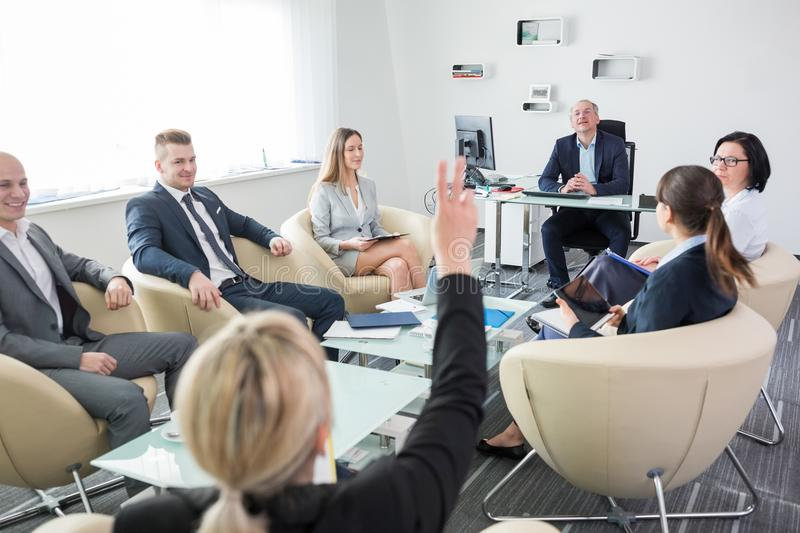Manager Looking At Executive Raising Hand During Meeting stock images