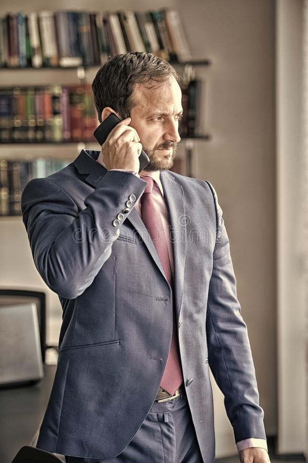 Manager man talk on smartphone. Manager man with beard in blue formal suit talk on smartphone at workplace desk in office. Business communication concept stock photography