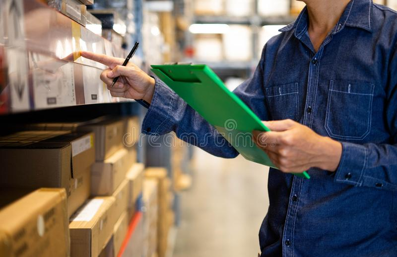 Manager man worker doing stocktaking of product management in cardboard box on shelves in warehouse. Physical inventory count.. stock photography
